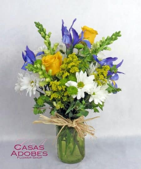 They will love this vibrant garden mix of blue iris, yellow roses and white daisy chrysanthemums accented with yellow solidago and green button chrysanthemums. This bouquet is artfully designed in a green mason jar shaped vase with a touch of raffia for a down home cottage feel.